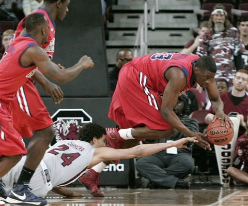 Mississippi's Murphy Holloway comes up with the ball as South Carolina's Michael Carrera (24) falls to the floor during the first half of an NCAA college basketball game Wednesday, Feb. 20, 2013, in Columbia, S.C. (AP Photo/Mary Ann Chastain)
