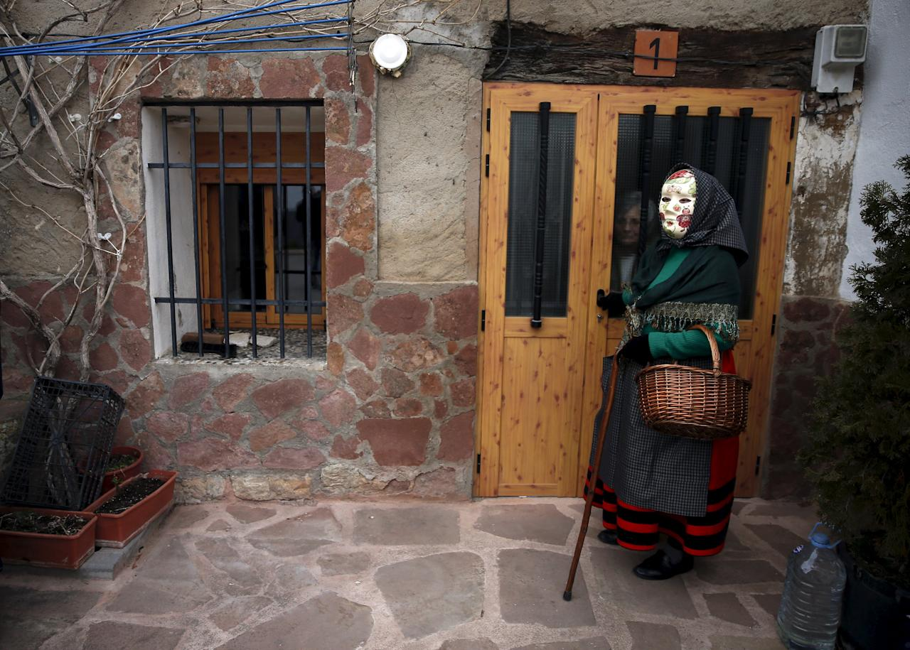 """A reveller, dressed as a """"Mascaritas"""", attends carnival celebrations in the village of Luzon"""