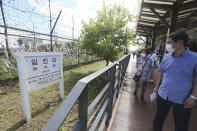 """People wearing face masks to help protect against the spread of the new coronavirus pass by a directional sign showing the distance to North Korea's city Kaesong and South Korea's capital Seoul at the Imjingak Pavilion in Paju, near the border with North Korea, Sunday, July 26, 2020. North Korean leader Kim Jong Un placed the city of Kaesong near the border with South Korea under total lockdown after a person was found with suspected COVID-19 symptoms, saying he believes """"the vicious virus"""" may have entered the country, state media reported Sunday. (AP Photo/Ahn Young-joon)"""