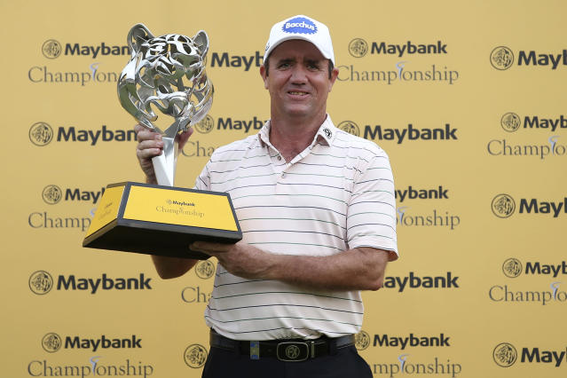 Scott Hend of Australia poses with his trophy after winning the Malaysia Golf Championship in Kuala Lumpur, Malaysia, Sunday, March 24, 2019. (AP Photo/Vincent Phoon)