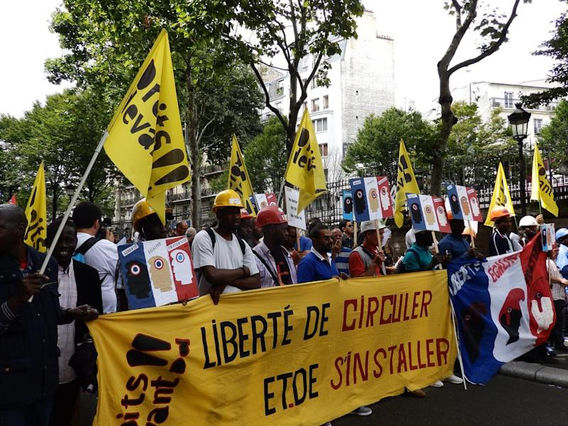 Protesters from the Droits Devant migrants' rights group at a Bastille Day march (Lizzie Dearden)