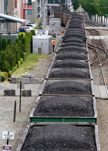 FILE - In this May 29, 2012, file photo, a train hauling coal to British Columbia heads north out of Seattle between office buildings, condos and the downtown waterfront. A coal-export terminal proposed in Washington state would increase cancer risk for some residents, make rail accidents more likely and add millions of metric tons of climate-changing greenhouse gas globally every year, according to an environmental study released Friday, April 28, 2017. (AP Photo/Elaine Thompson, File)