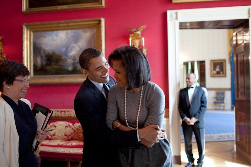 President Barack Obama hugs first lady Michelle Obama in the Red Room while senior advisor Valerie Jarrett smiles at the White House on March 20, 2009.