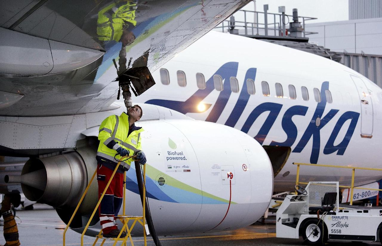 FILE - In this Monday, Nov. 14, 2016, photo, fueling manager Jarid Svraka looks on as he fuels an Alaska Airlines Boeing 737-800 jet with a new, blended alternative jet fuel, at Seattle-Tacoma International Airport in SeaTac, Wash. On Tuesday, Dec. 6, 2016, Alaska Airlines said it has won government approval to buy rival Virgin America after agreeing to reduce its flight-selling partnership with American Airlines. (AP Photo/Elaine Thompson, File)