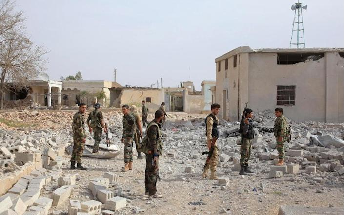 Syrian soldiers walk near debris on the eastern outskirts of the northern city of Aleppo (AFP Photo/George Ourfalian)