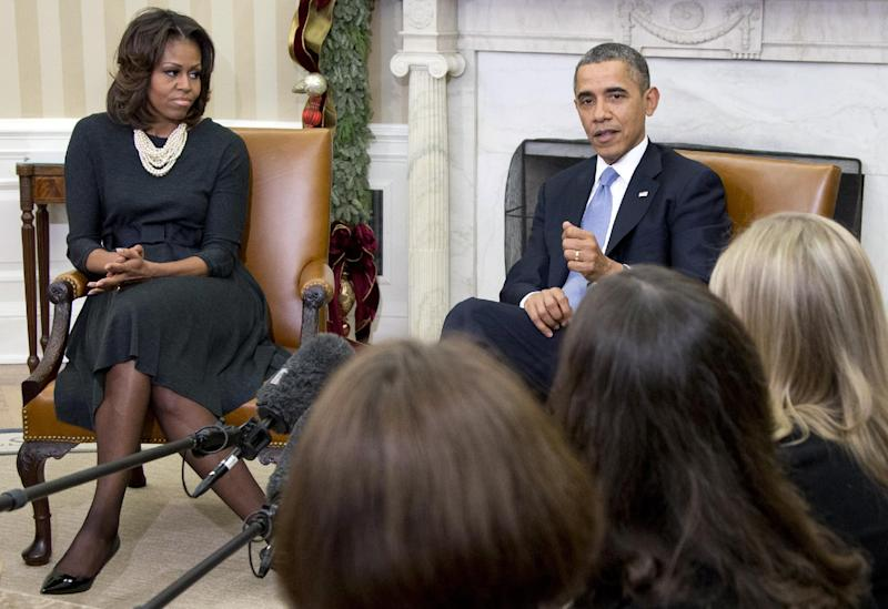 President Barack Obama, right, gestures as he speaks to the media as he and first lady Michelle Obama meet with a group of mothers in the Oval Office of the White House in Washington, Wednesday, Dec. 18, 2013, to discuss how health care reform could benefit their families. (AP Photo/Carolyn Kaster)