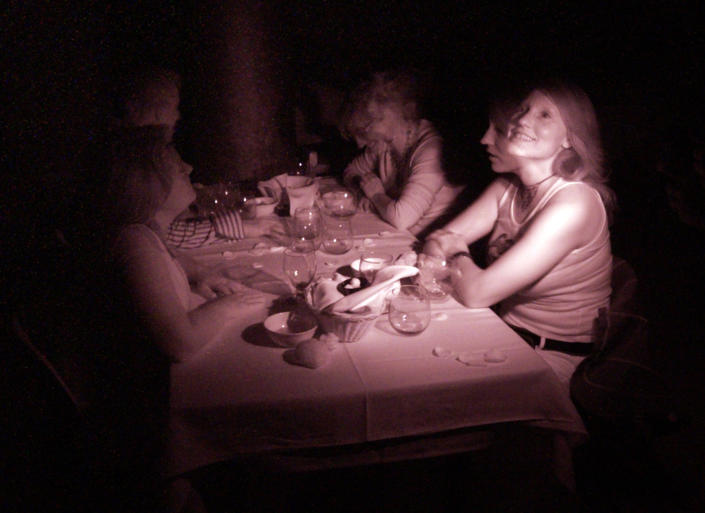 In this false color infrared flashed time exposure image, customers Megan Phares (L), Jamey Titone, (2nd L), Stephanie Wandke (2nd R), and Bonnie Titone (R) experience dining in complete darkness at Opaque in West Hollywood, November 25, 2006. In this weekly dining experience, guests are served a three course gourmet meal in a pitch black dining room by blind waiters. REUTERS/Jason Redmond