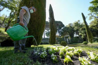 A worker waters flowers in the section of the gardens of the Papal Palace where Pope John Paul II used to gather in prayer, next to a statue of the Madonna, in Castel Gandolfo, some 30 kilometers southeast of Rome, Saturday, May 29, 2021. As Covid-19 restrictions are slowly being lifted in Italy, thousands of people are returning to see the extensive gardens and apartments at the Papal Palace of Castel Gandolfo in the Alban Hills near Rome, that for hundreds of years have been the summer retreat for Popes seeking to escape the suffocating heat of Rome. (AP Photo/Andrew Medichini)