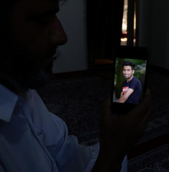 Altaf Ahmad Marazi holds up a picture on a phone of his son Osaib Altaf, 17, who died after jumping in a river to escape security forces in Srinagar (Zubair Sofi/The Independent)