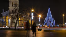 Visitors look at the Christmas tree in Cathedral Square in Vilnius, Lithuania, Saturday, Dec. 5, 2020. (AP Photo/Mindaugas Kulbis)
