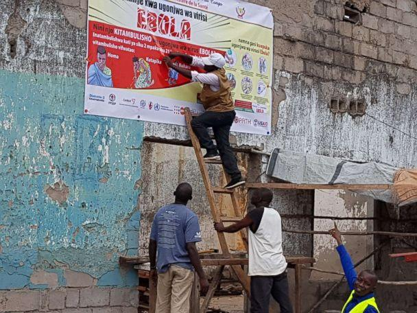PHOTO: Workers fix an Ebola awareness poster in Tchomia, Democratic Republic of Congo, to raise awareness about Ebola in the local community, Oct. 9, 2018. (Aboulaye Cisse/WHO via Reuters)