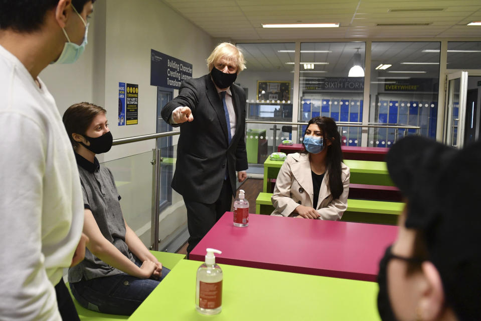 Britain's Prime Minister Boris Johnson, background centre left, meets Sixth form students during a visit to Accrington Academy in Accrington, England, Thursday, Feb. 25, 2021 as they prepare for the return of all pupils on March 8, (Anthony Devlin/Pool Photo via AP)