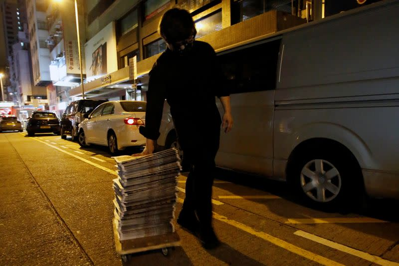 Supporter of Apple Daily newspaper wheels a stack of the June 18 edition he purchased from a newspaper seller in Hong Kong