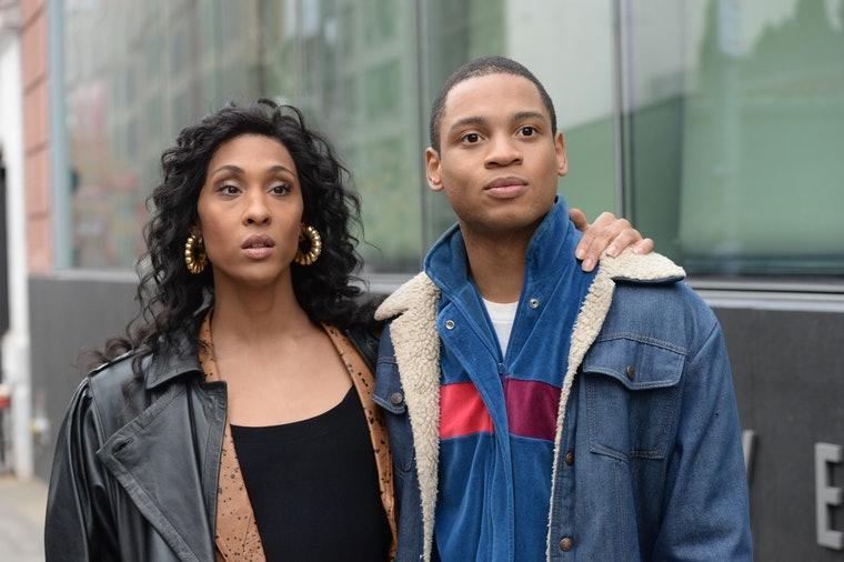 Blanca and Damon from Pose stand beside each other. She is wearing a black shirt and brown leather jacket. He is wearing a blue and white wool coat and red and blue button down shirt