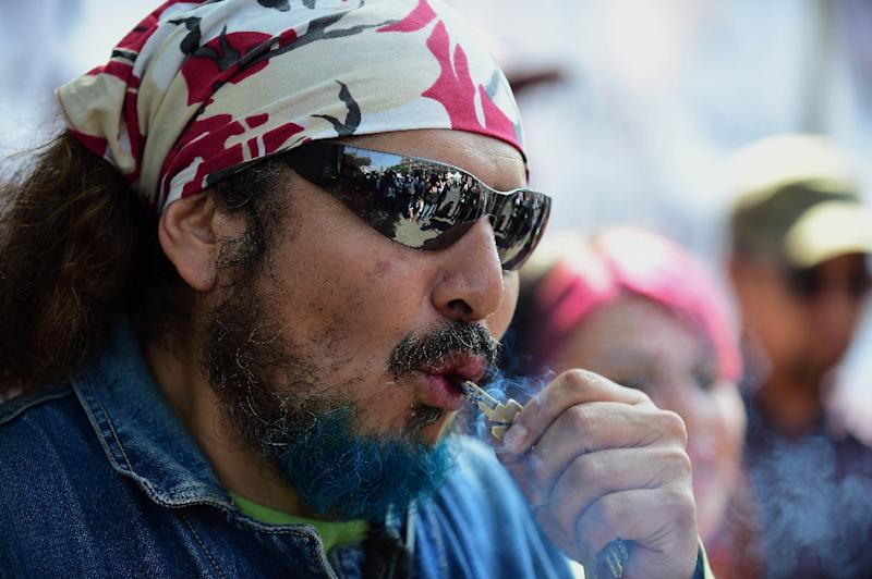 A man smokes marijuana during a rally in front of the Supreme Court of Justice in Mexico City on November 4, 2015 (AFP Photo/ALFREDO ESTRELLA)