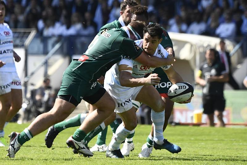 Racing 92 fly-half Dan Carter (R) is tackled by Pau hooker Quentin Lespiaucq during the French Top 14 match at the Yves du Manoir Stadium in Colombes, outside Paris, on April 9, 2017 (AFP Photo/Christophe SIMON)