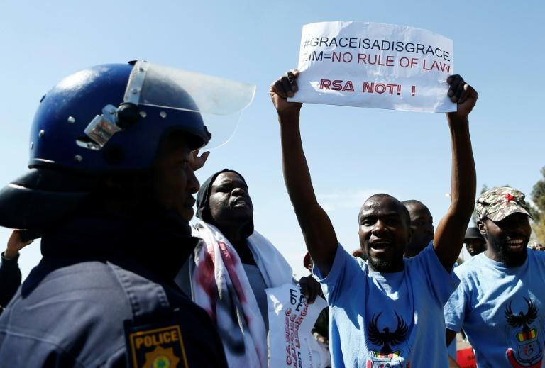 """Protesters gathered outside a summit of regional leaders in Pretoria which Zimbabwe's first lady had been due to attend, some waving signs reading """"Grace is a disgrace"""""""