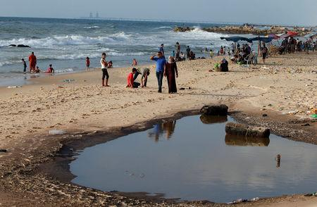 Palestinians walk past a pool of sewage on a beach in the northern Gaza Strip July 13, 2018. REUTERS/Mohammed Salem