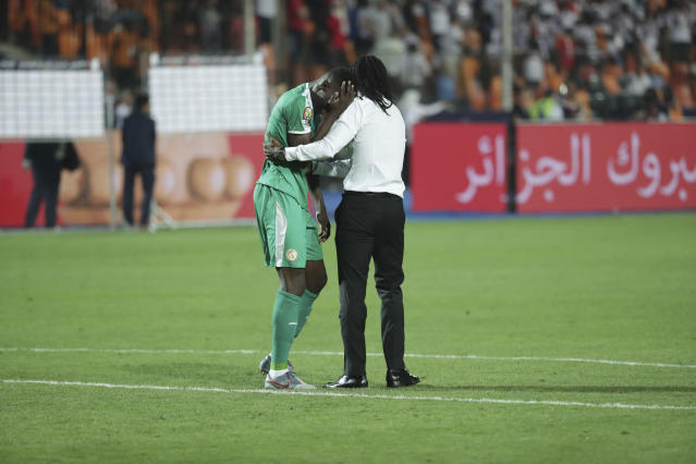 Senegal's head coach Aliou Cisse hugs his player after loosing the African Cup of Nations final soccer match between Algeria and Senegal in Cairo International stadium in Cairo, Egypt, Friday, July 19, 2019. (AP Photo/Hassan Ammar)