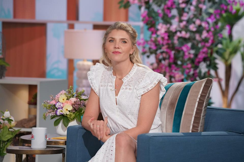 Amanda Kloots, pictured here wearing a white dress on the set of The Talk, opened up about hating the word widow