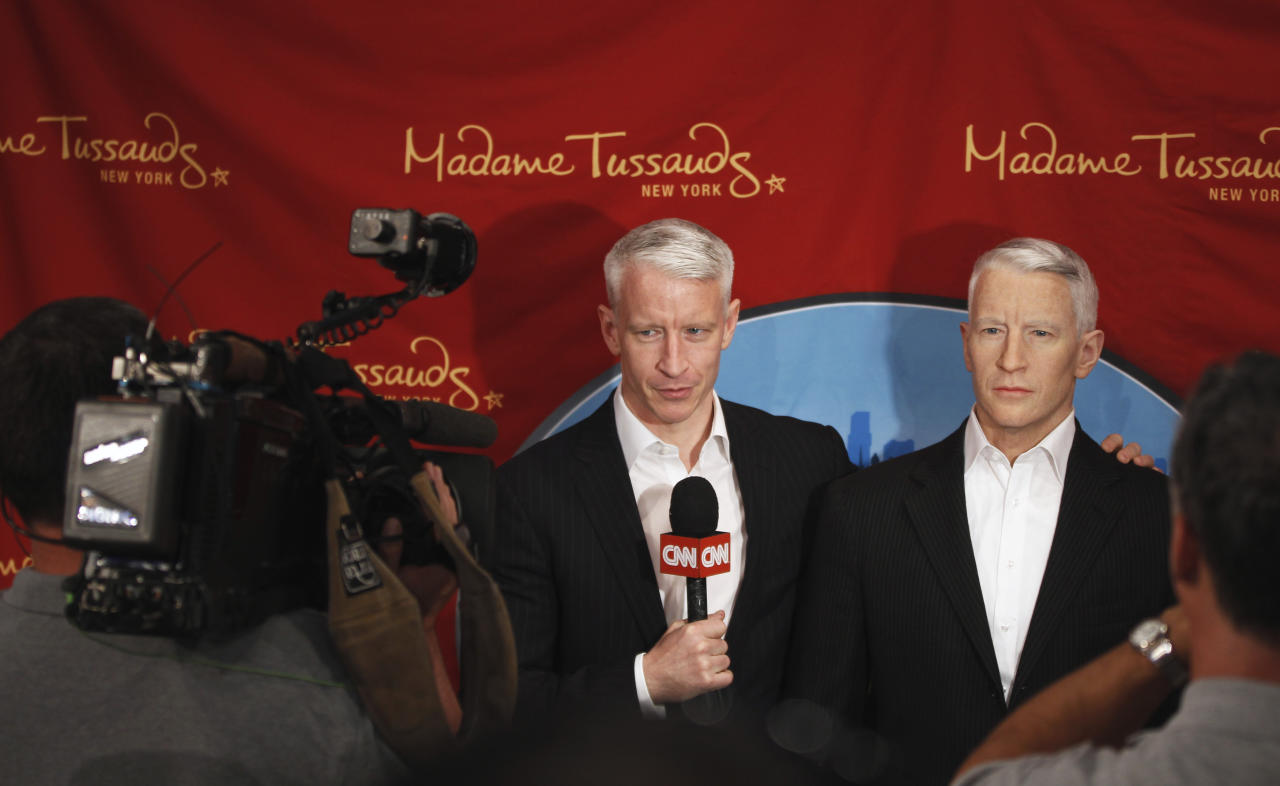 Television journalist Anderson Cooper speaks to a CNN team as he poses with his wax figure after it was unveiled at Madame Tussauds in New York, September 14, 2011. REUTERS/Lucas Jackson