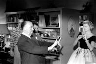<p>Alfred Hitchcock plans out a shot while filming <em>Rear Window </em>with Grace Kelly and James Stewart. </p>