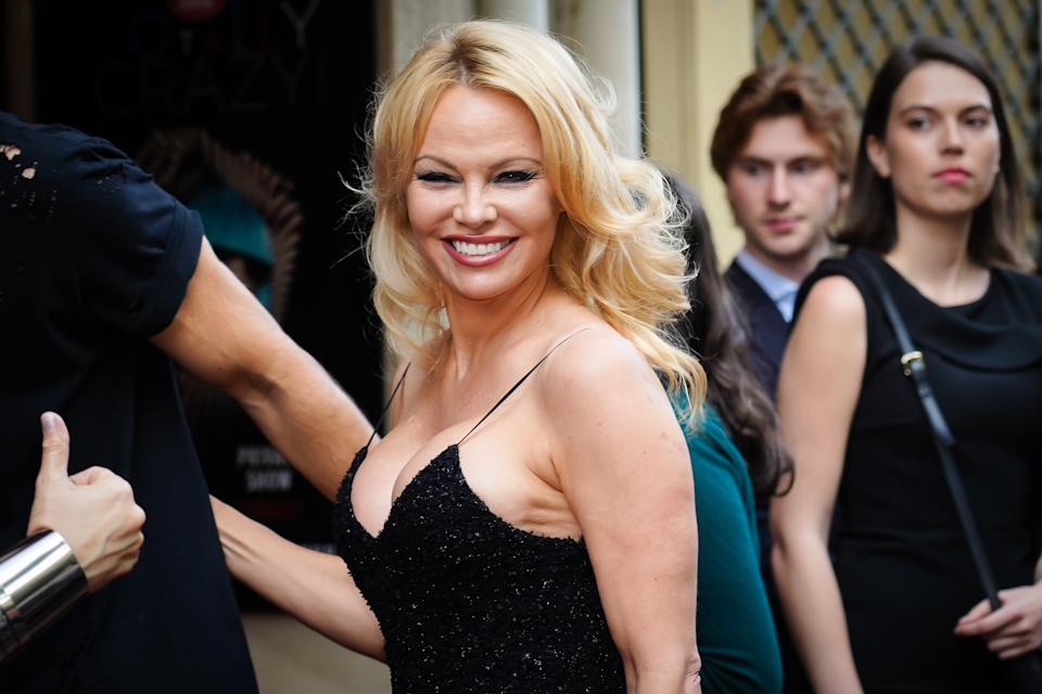 Pamela Anderson in a black dress smiling at the camera