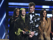 "Billie Eilish, left, and Finneas O'Connell accept the award for song of the year for ""Bad Guy"" at the 62nd annual Grammy Awards on Sunday, Jan. 26, 2020, in Los Angeles. At right looking on is presenter Karen Fairchild. (Photo by Matt Sayles/Invision/AP)"