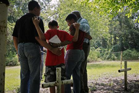 L-R: Steven Barnes, 61, of Smyrna, Georgia, his son Jason Due-Barnes, 9, wife Tananarive Due, 47, and her father John Due, 78, of Atlanta, Georgia, embrace during a memorial ceremony at the Boot Hill cemetery at the now closed Arthur G. Dozier School for Boys in Marianna, Florida, August 31, 2013. REUTERS/Edmund D Fountain/Pool