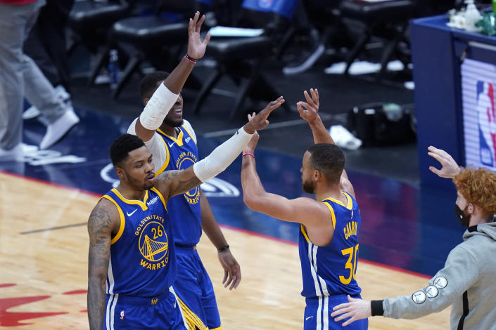 Golden State Warriors guard Stephen Curry (30) celebrates with forward Kent Bazemore (26) and center Kevon Looney during a run in the first half of an NBA basketball game against the New Orleans Pelicans in New Orleans, Monday, May 3, 2021. (AP Photo/Gerald Herbert)