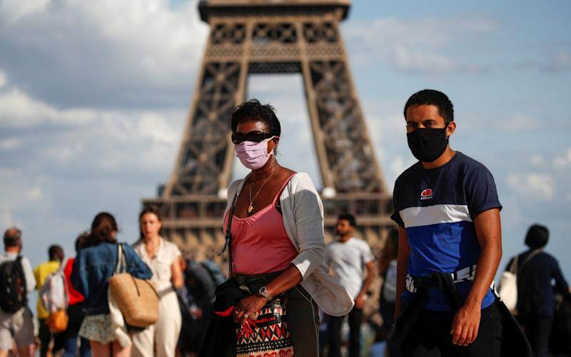 People wearing protective face masks walk at the Trocadero square near the Eiffel Tower in Paris - REUTERS/Gonzalo Fuentes