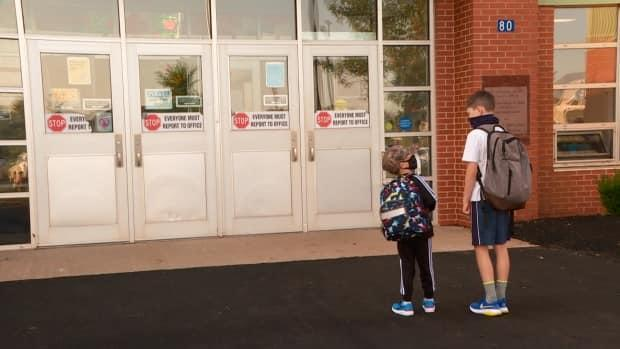 After two weeks in self-isolation, five-year-old Nolan Innis, left, and 11-year-old Blake Innis, right, were happy to head back to school Friday.  (Sheehan Desjardins/CBC - image credit)