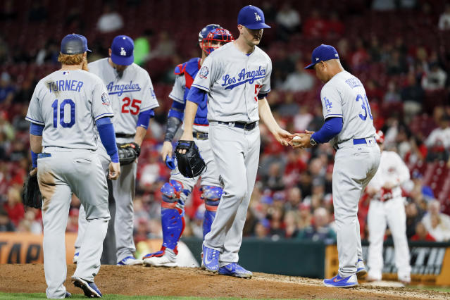 Los Angeles Dodgers starting pitcher Alex Wood , center, is relieved by manager Dave Roberts (30) in the fourth inning of a baseball game against the Cincinnati Reds, Monday, Sept. 10, 2018, in Cincinnati. (AP Photo/John Minchillo)