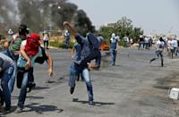 Palestinian protesters hurl rocks at Israeli security forces during clashes near the Jewish settlement of Beit El on July 24, 2017