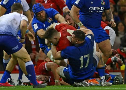 Wales wing Josh Adams (centre) dives over the line to score his third try during the Six Nations match against Italy in Cardiff on February 1, 2019
