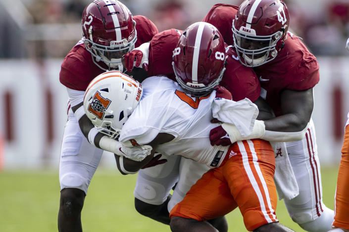 Alabama defensive back DeMarcco Hellams (2), linebacker Christian Harris (8) and defensive lineman Byron Young (47) stop Mercer quarterback Fred Payton (4) during the first half of an NCAA college football game, Saturday, Sept. 11, 2021, in Tuscaloosa, Ala. (AP Photo/Vasha Hunt)