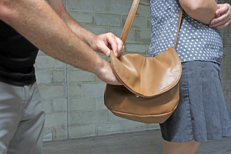 Male thief pickpocketing from a womans purse while waiting in a street.