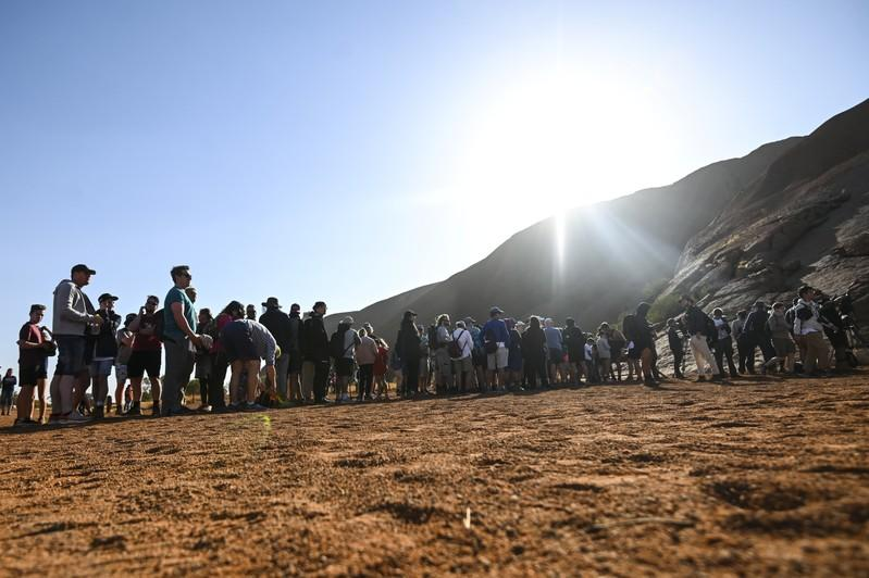Tourists line up to climb Uluru, formerly known as Ayers Rock, at Uluru-Kata Tjuta National Park in the Northern Territory