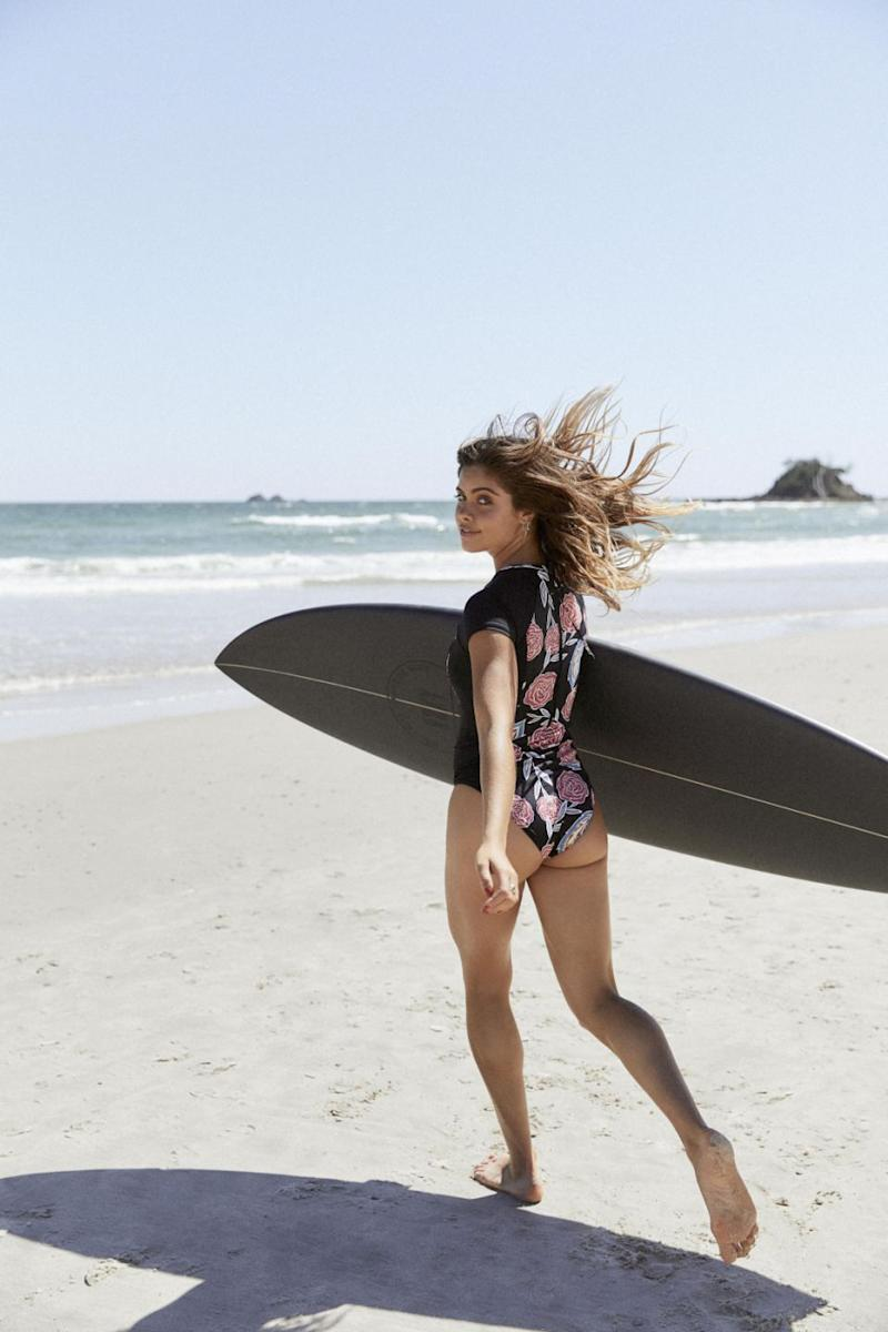 The 22-year-old poses with a Roxy surfboard walking towards the ocean. Source: Ming Nom Chong Photography
