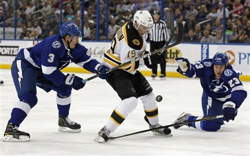 Boston Bruins' Tyler Seguin, center, is checked by Tampa Bay Lightning's Keith Aulie, left, and Mike Commodore during the first period of an NHL hockey game Tuesday, March 13, 2012, in Tampa, Fla. (AP Photo/Mike Carlson)
