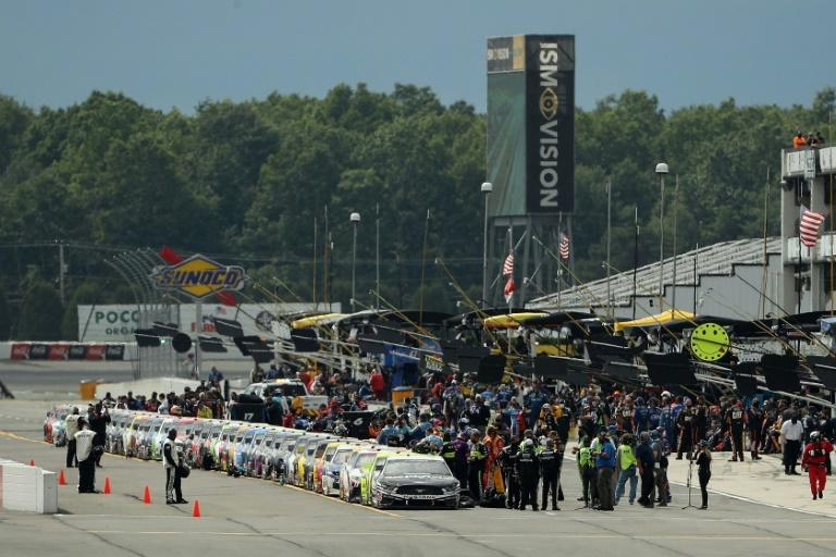 Drivers and crew stand on the grid during pre-race ceremonies at the NASCAR Cup Series race at Pocono Raceway in Long Pond, Pennsylvania