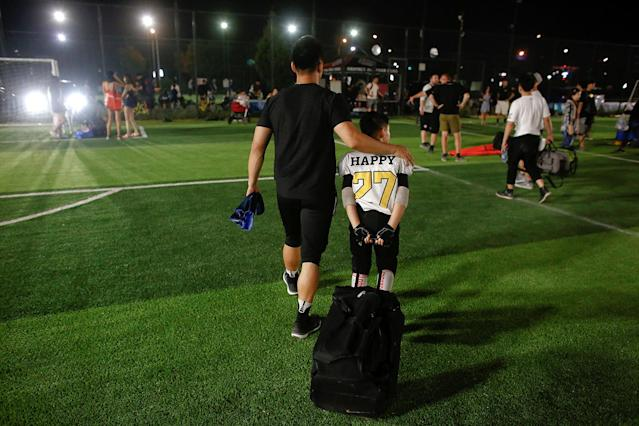 <p>An Eagles player leaves the field after his team defeated the Sharklets in the Future League American football youth league in Beijing, May 26, 2017. (Photo: Thomas Peter/Reuters) </p>