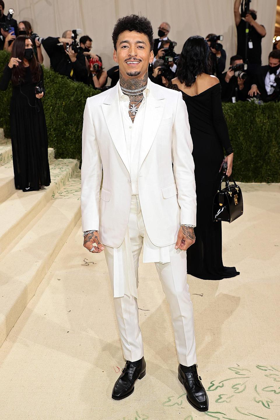 <p>The Olympic skateboarder paired his all-white suit look with black boots and layers of sparkling necklaces.</p>