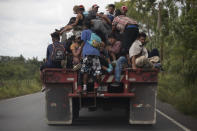 FILE - In this Oct. 2, 2020 file photo, migrants ride on the back of a freight truck that slowed down to give them an opportunity to jump on in Rio Dulce, Guatemala. Mauro Verzzeletti, director of the Casa del Migrante in Guatemala City, said the storms Eta and Iota will increase poverty on top of the violence people already faced, forcing more to migrate. (AP Photo/Moises Castillo, File)
