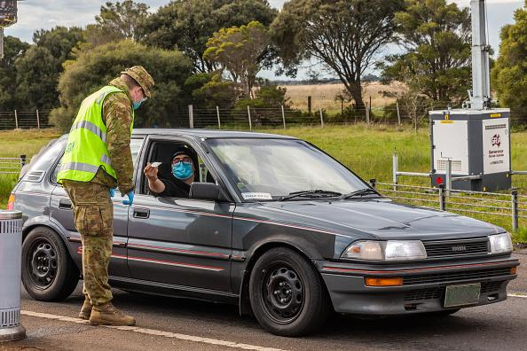 An Australian Defence Force personnel checks the permit and ID of a driver at a checkpoint in Little River for traffic coming from Melbourne into Geelong and the Bellarine Peninsula.