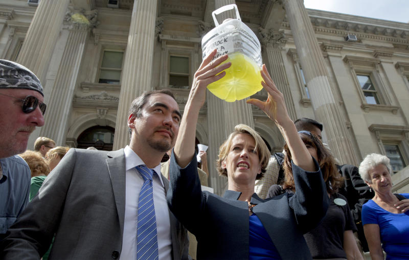 New York State democratic governor candidate Zephyr Teachout (R) holds a a bottle of frack contaminated water as lieutenant governor running mate Tim Wu (2nd L) looks on during a campaign event in New York September 3, 2014. REUTERS/Brendan McDermid/File Photo