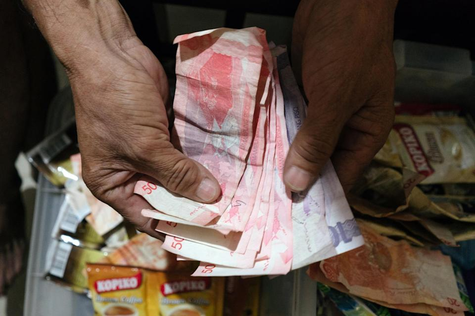 A man counts Philippine Peso bills inside a store in Manila, Philippines. (Photo: Getty Images)