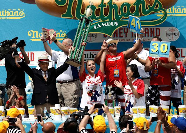 <p>US competitive eater Miki Sudo (C) raises the trophy after winning the Women's Nathan's Famous Fourth of July International Hot-dog eating contest in Coney Island, New York on July 4, 2017. Sudo won by consuming 41 hotdogs. (Peter Foley/EPA/Shutterstock) </p>