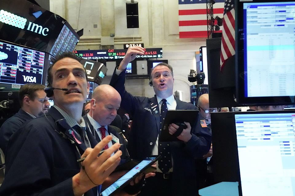 Traders work on the floor at the opening bell of the Dow Industrial Average at the New York Stock Exchange on March 18, 2020 in New York. - Wall Street stocks resumed their downward slide early Wednesday as the economic toll mounts from the rapid near-shutdown of key industrial and services sectors.About 15 minutes into trading, the Dow Jones Industrial Average stood at 20,040.66, down around 1,200 points or 5.6 percent. (Photo by Bryan R. Smith / AFP) (Photo by BRYAN R. SMITH/AFP via Getty Images)