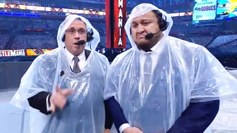Commentators Michael Cole (pictured left) and Samoan Joe (pictured right) at WrestleMania 37 in ponchos.